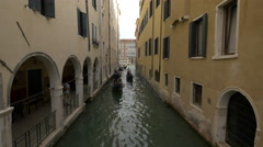 Rowing gondolas by a building with arches in Venice Stock Footage
