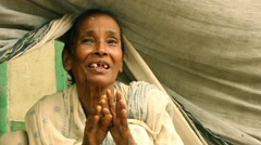 Elderly Indian woman smiles and fold hands in gratitude upon receiving some v Stock Footage