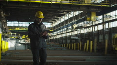 Technician in Hard Hat in Industrial Environment. Holding Tablet in Hands. - stock footage