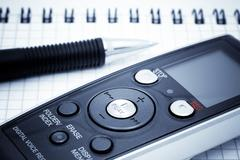 Journalist equipment. Digital voice recorder, pen, notebook - stock photo