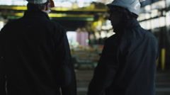 Two Workers Hard Hats Walking in Industrial Area with Cranes - stock footage