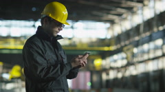 Technician in Hard Hat in using Phone in Industrial Environment. Holding Tablet  Stock Footage