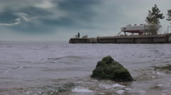 Fisherman fishing rod on the pier, a storm on the river, 4k Stock Footage