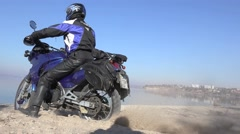 Blue bike rides along the river, under the wheels of the sand flies Stock Footage