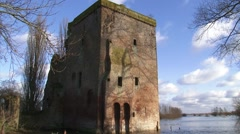 Ruins great tower of a medieval Castle + tilt down inundated floodplains Stock Footage