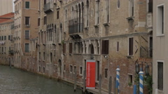White boat sailing along a brick building in Venice Stock Footage