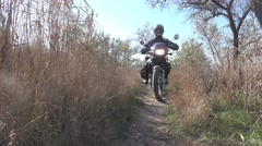 Motorcyclist goes on a footpath among the dry reeds, autumn, 4k Stock Footage