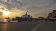 People walking by a yacht anchored in Venice at sunset Stock Footage