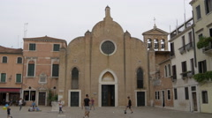 Teenagers playing football in front of San Giovanni in Bragora Church in Venice - stock footage