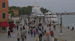 People walking by two yachts anchored on the waterfront in Venice - stock footage