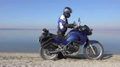 The motorcyclist in a helmet and blue bike stands on the bank of the river Stock Footage