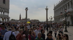 Tourists walking around the columns with statues in St Mark's Square, Venice Stock Footage