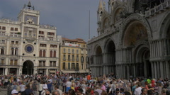 Tourists walking by the St Mark's Basilica and Torre dell'Orologio in Venice Stock Footage