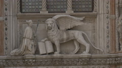 Lion with wings and priest sculptures on Palazzo Ducale, Venice Stock Footage
