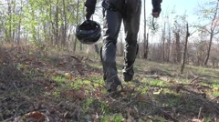 Motorcyclist in gear with helmet in his hand goes in the autumn woods Stock Footage