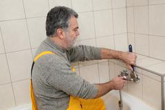 Plumber works in a bathroom bath toob faucet fixing Stock Photos