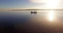 fishing boat leaving harbour in the morning sun - stock footage