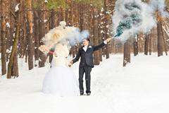 Wedding couple with color smoke in the winter park. Colour bomb - stock photo