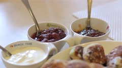Stock Video Footage of Cottage cheese pancakes with raisins, sour cream and jam on the table