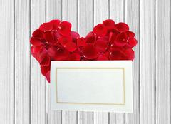 Heart from red rose petals and white card on wooden table Stock Photos