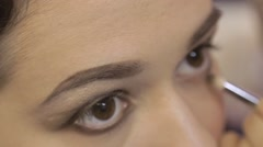 makeup artist makes eyeliner for a girl - stock footage