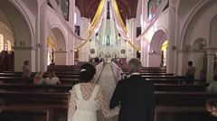 Father leads his daughter to the altar in the church Stock Footage