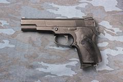 Black pneumatic pistol on a camouflage background. - stock photo