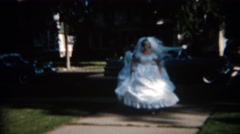 1965: Bride tests out giant white flowing dress in city park. BUFFALO, NEW YORK Stock Footage