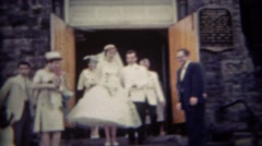 1956: Newlywed couple leaving church steps rice tossed. BUFFALO, NEW YORK Stock Footage