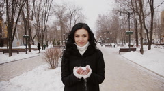 Happy girl in winter clothes throws snow and rejoices in the park at winter. Stock Footage