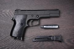 Black pneumatic pistol against a dark background. - stock photo