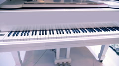 Brilliant white piano with the lid open for better sound - stock footage