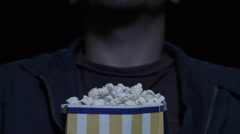 CU, pan up shot of young man eating popcorn watching a movie at the cinema - stock footage