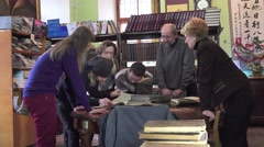 Group of people, men and women look old books on a table in library, 4k Stock Footage