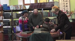 Group of people, men and women, look strinam books on the table in library Stock Footage