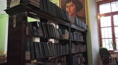 Rack of old books in the library with a portrait of Copernicus, 4k Stock Footage