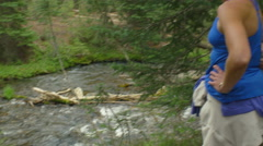 Woman watches her dogs play in the river Stock Footage