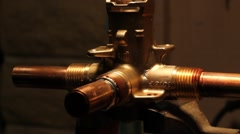 A plumber sweating copper pipe onto a valve Stock Footage