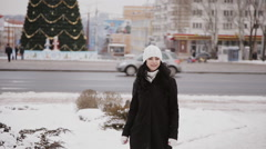 Girl goes on a city on a background of Christmas tree Stock Footage