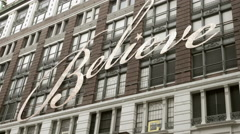 believe sign on Macy's department store in Manhattan, tilting down street 4K NYC - stock footage