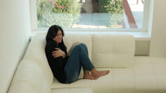 Woman suffering strong stomac ache sitting on sofa at home Stock Footage