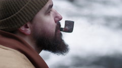 Portrait of bearded woodsman smoking a pipe by the river - stock footage