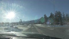 4k Car Windshield View Drive Through Small Town Jasper Snow Mountains Lens Flare Stock Footage