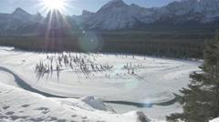 4k Beautiful Mountain Scenery Frozen Lake Snow Trees Icy Peaks Jasper Lens Flare Stock Footage