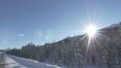 4k Driving Along Fir Trees Forest Mountains Snow Road Jasper Lens Flare Sun Stock Footage
