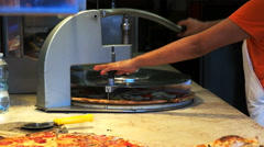 Waitress using a machine to cut pizza into slices at a restaurant, venice Stock Footage