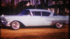 3086 brand new 1957 Cadillac Coupe Deville in driveway-vintage film home movie Stock Footage