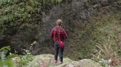 Man kneels and takes a picture at the edge of a waterfall cliff Stock Footage
