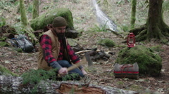 Bearded backpacking man chops firewood against a log - stock footage