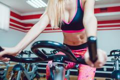Young blonde woman on a stationary bike. - stock photo